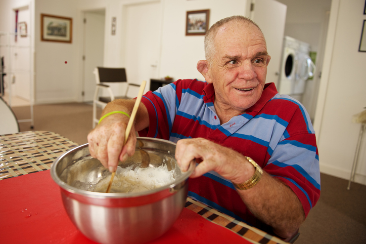 Smiling gentleman at home in a red and blue striped shirt mixing ingredient in a large metal bowl