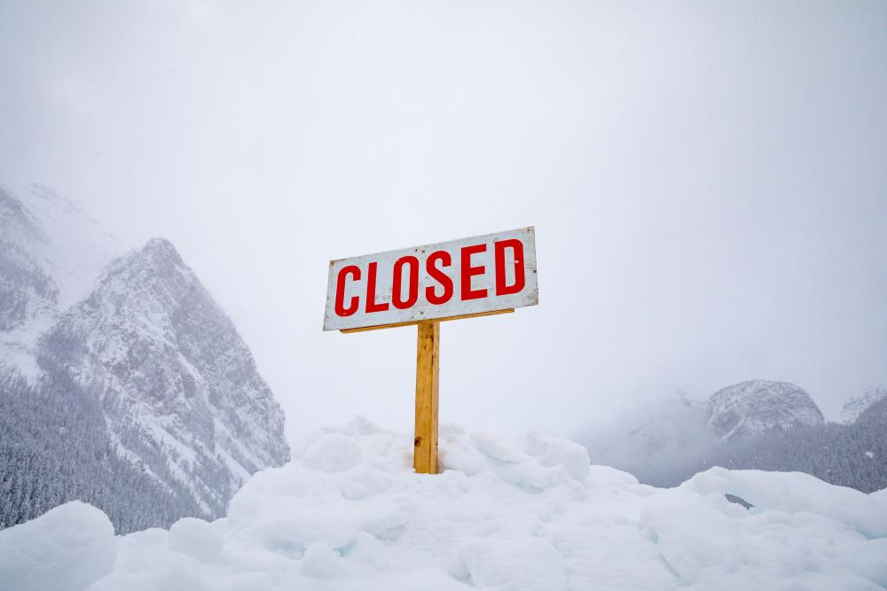 Rectangular, white closed sign with red lettering on a wood post sticking out of a large snow pile