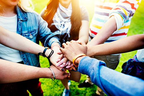 group of people hands together - support