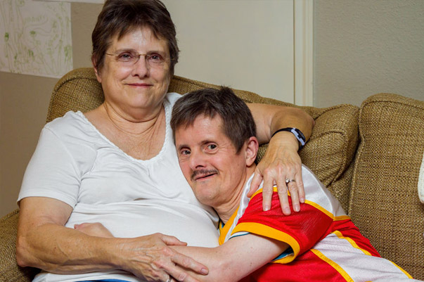 adult man with down syndrome on couch with relative